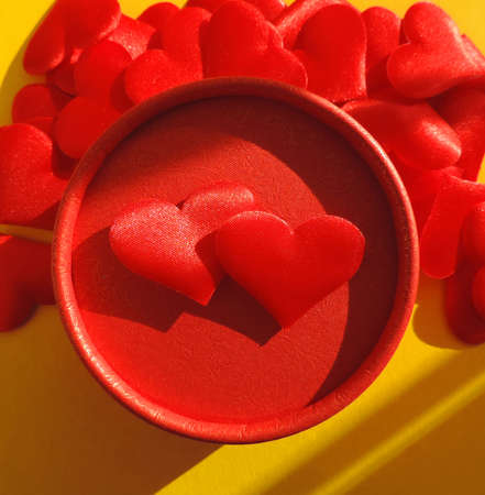 red gift box and red hearts on yellow background in natural light of sun rays and shadows Symbol of love, romantic. Festive gift card on valentines day. light and shadow symbolizes ying and yang