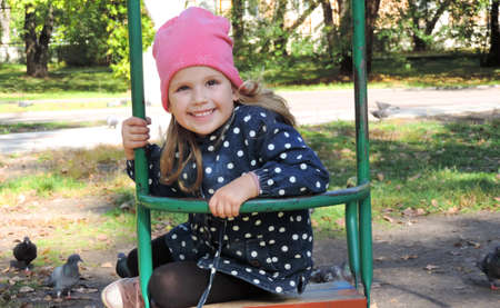 little girl child in autumn clothes and a pink hat in the park swinging on a swing and laughing