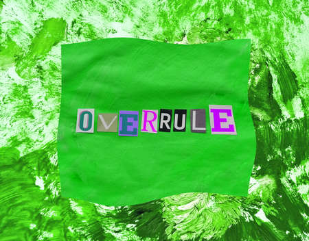 Overrule word from paper magazins letters on green distorted frame and chaotic paint strokes. Grunge textured background Stock fotó