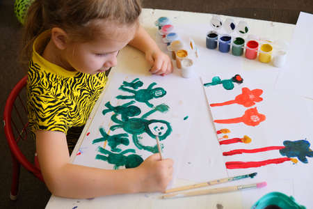 Child making homemade greeting card. A little girl paints happy family as a gift for Mothers Day or Valentines day. Traditional play concept. Arts and crafts concept.