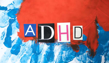 ADHD. Abbreviation ADHD from paper letters. Chaotic blue red stripes background. ADHD is Attention deficit hyperactivity disorder