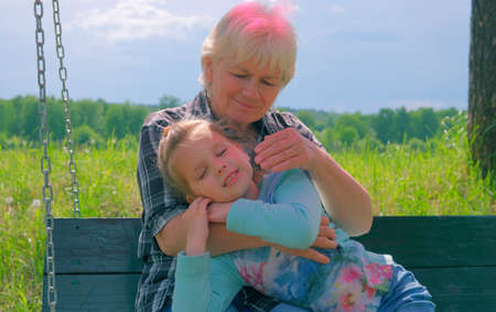 Loving cute granddaughter hugging her grandmother. Happy family. Having good times with grandparent outdoors