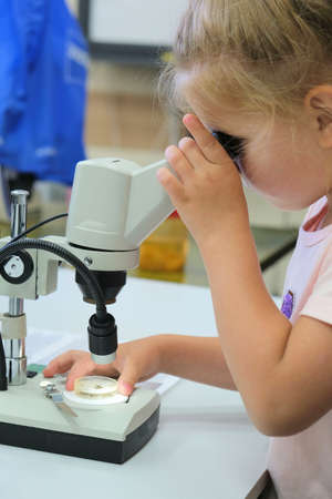 Little girl conducts experiment with microscope, looks through a microscope live microorganisms. Micro biology for young children. Stock Photo
