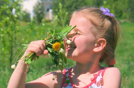 Happy little girl sniffs summer flowers in a field. Happy child enjoying nature outdoors
