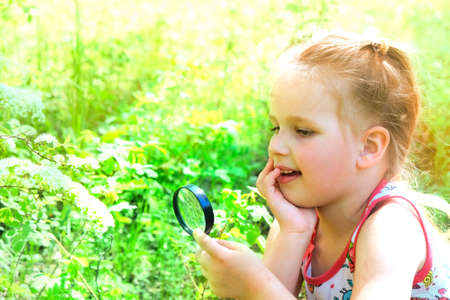 Little girl with a magnifying glass in her hand investigate details of nature. Summer time outdoor kids activity and learning concept. Banque d'images