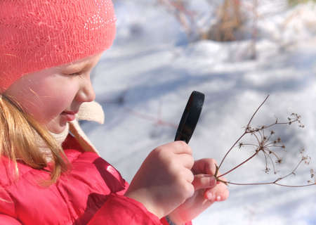 Little girl in warm winter clothes with a magnifying glass in her hand investigate details of nature. Winter outdoor kids activity and learning concept