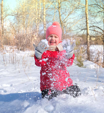 Winter fun, little girl play with snow on a winter day. Winter time. Young girl in red coat happily throw snow up above herself.