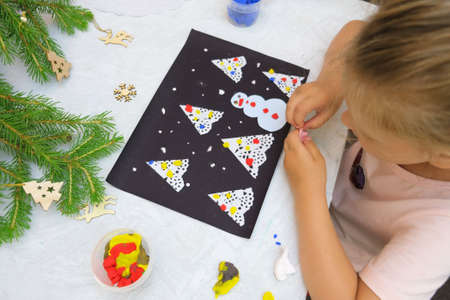 Child making a greeting card Christmas paper and  plasticine craft. Craft for children. Nice greeting card with a Christmas snowy night with fir trees and snowman. Top view