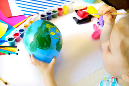 Child drawing pattern of flower and plants on the balloon. Earth day. Arts  crafts concept. art learning and education