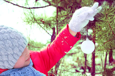 Child hangs a decoration on a Christmas tree outdoors. Christmas tree decor Banque d'images