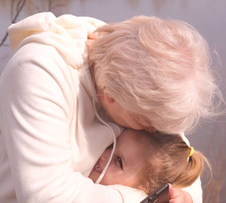 Loving grandmother hugging her granddaughter. Having good times with grandparent outdoors Banque d'images