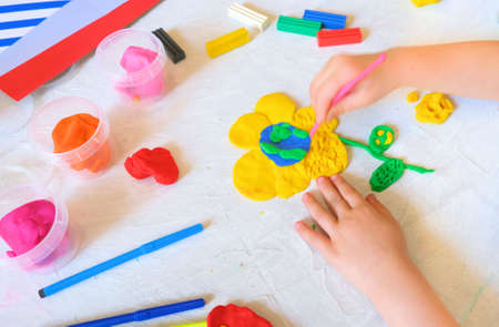 Little girl making flower with center earth planet shape from plasticine, Home Education game with clay. Early development and ecology concept. Educational and entertaining classes with children
