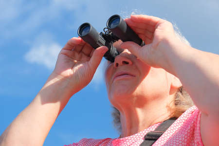 Low angle view of a senior woman with binoculars outdoors, birdwatching Banque d'images