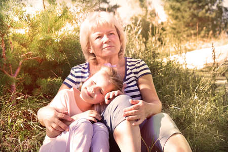 Loving cute granddaughter hugging her grandmother. Happy family. Having good times with grandparent outdoors Banque d'images