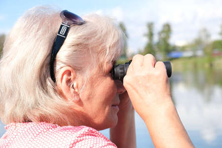 senior woman with binoculars outdoors