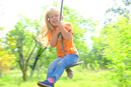 Child having fun outdoors swinging on wooden homemade swing tied to a tree with a rope in spring or autumn.