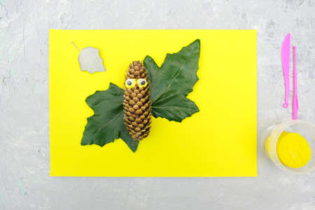 Autumn crafts. Child making fun butterfly from natural cone and leaves use paper and plasticine. Back to school. Ideas for children's art
