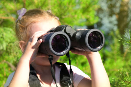 Little girl using binoculars in the forest. Exploring the world. Outdoor activities. Banque d'images