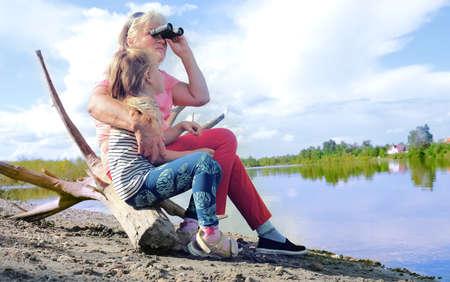 Little girl with her grandmother looking through binoculars outdoor Banque d'images