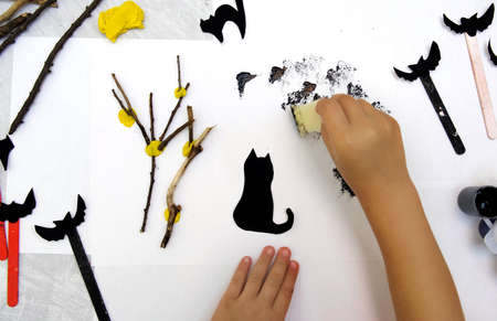 Child making card for the holiday Halloween. Funny crafts from paper, natural tree twigs and painting with a sponge. The concept for Halloween. DIY. Children's art project, a craft for children.
