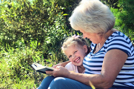 Grandmother reading to her granddaughter child book outdoors. Happy family concept