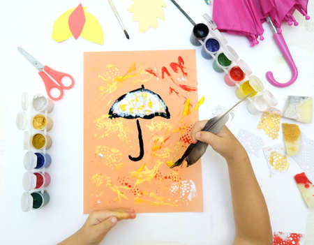 Autumnal card. Child paint umbrella and abstract autumn park use sponge and birds feather like a paintbrush, crafts for kids.