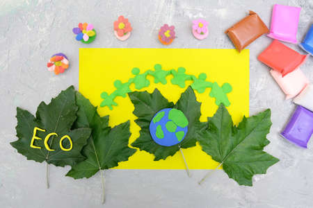 Child made Earth planet from plasticine and card from paper and natural leaves. Protection of environment, Save our planet. Ecology concept. Concept of art learning and education