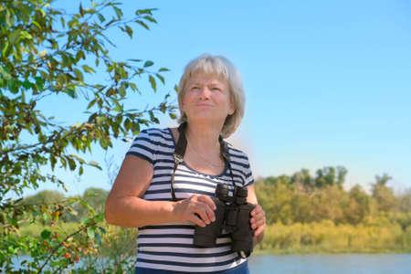 senior woman with binoculars outdoors, birdwatching