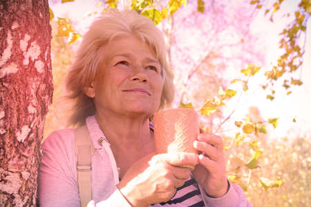 Satisfied senior woman breathing fresh air holding a coffee cup standing outdoors in the park