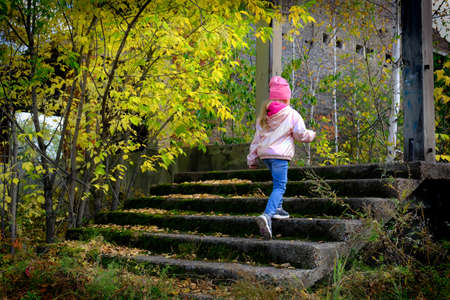 Child climbs the destroyed old staircase of an abandoned building, a danger to children playing without parental supervision