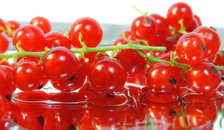 Red currant berries on a mirror surface and the reflection in water drops is distorted Banque d'images