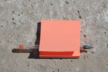 blank orange sticker forms with place for text, pen, concrete peeling surface