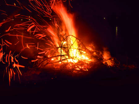 Motion blur of sparkles of campfire with firewood on dark night background Banque d'images