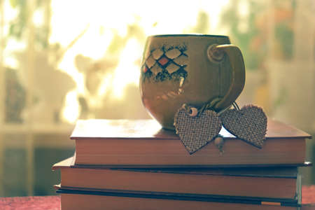 Valentines day concept. Cup and two hearts on books, retro effect noise and grain Banque d'images