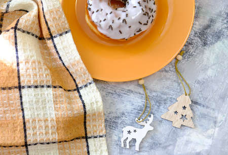 Donut in the glaze on orange plate. Christmas wooden toys on the table, Christmas morning. Top view copy space