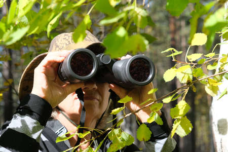 Active senior woman with binoculars in the forest Banque d'images