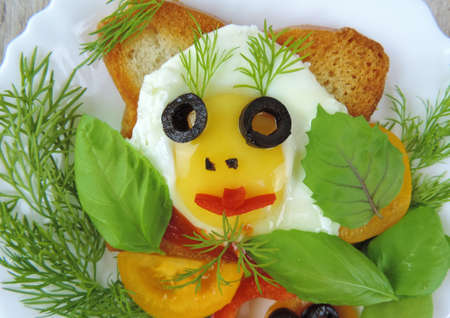 fried eggs face shape with olives eyes, on fried toast with vegetables and herbs, fun food concept for a child, selective focus
