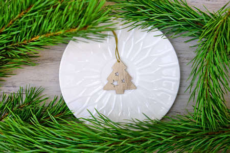 Christmas table setting with plate and Christmas wooden tree toy and natural branches. Top view.