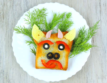 Fun sandwich with slice meat sausage, cheese, bell pepper, olives, dill on plate. funny baby food in the form of an animal face