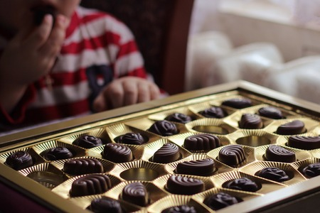 Closeup view of box of chocolates.child eating candy