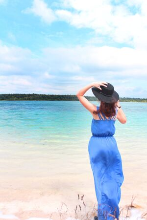 a girl in a hat and a long blue dress on the shore of a blue lake. summer holiday