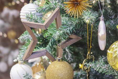 Christmas toy wooden star on the branch of the Christmas tree. decorated Christmas tree to celebrate the new year. festive mood. happy new year. Banco de Imagens