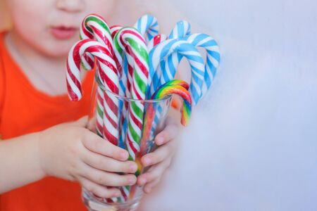 a child with lots of candy. striped candy cane. festive mood Imagens