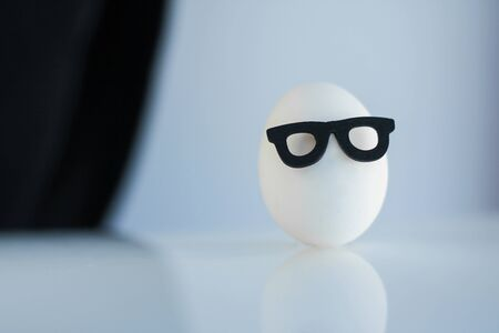 one white egg in black-rimmed glasses on a black and white background 스톡 콘텐츠