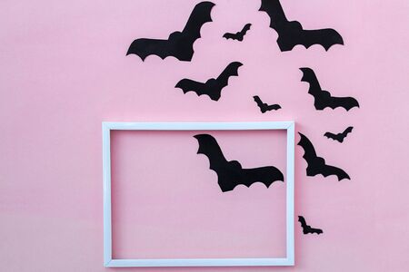 black paper bats and white frame on pink background.