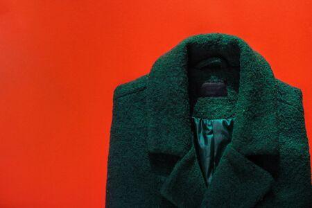 green womens coat on a red background. autumn wardrobe Zdjęcie Seryjne