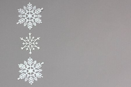 three white decorative snowflakes on a gray background. Christmas and New Year, a place for text