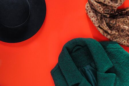 Autumn Fashion Concept. Stylish Lady Clothes. green women's coat, black hat and scarf on a red background. autumn wardrobe, autumn warm clothing, flatlay, top view
