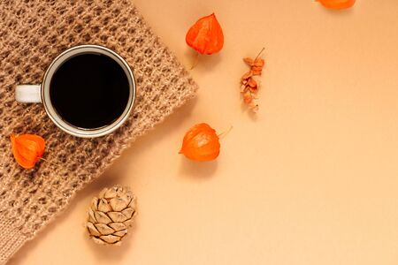 autumn background. a knitted blanket, a up of coffee, physalis and pine nuts. Hello autumn. Flat lay, top view, copy space.