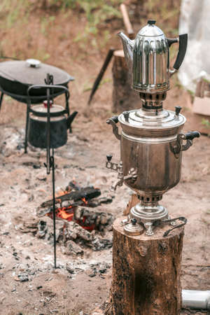 outdoor recreation in a campsite after a hike, making tea on the fire, a samovar on the street kindled with coal. Banco de Imagens